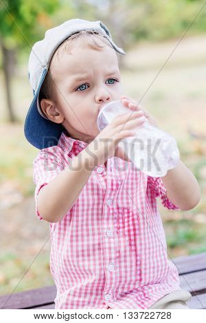 cute toddler boy drinking water outdoors in summer time