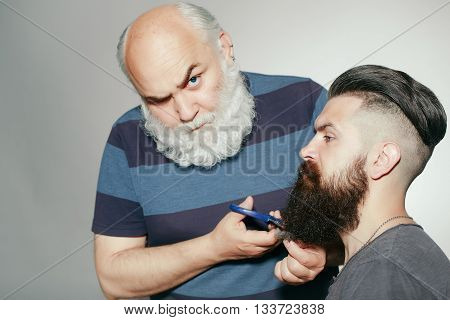 Old and young bearded men with long beard white and brown in studio on grey background. Hairdresser with scissors cutting beard