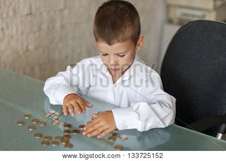 Little caucasian manager boy counting coins on desk in office