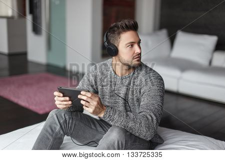 Young caucasian man caught listening music on tablet indoor