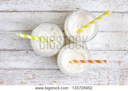 Yogurt in three small jars with straws. top view
