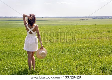 young girl with long dark hair standing on a green field with green grass backs to the camera in a short white summer dress and straw hat and then removes it. throws up his hands and enjoying nature. in the right corner of the screen