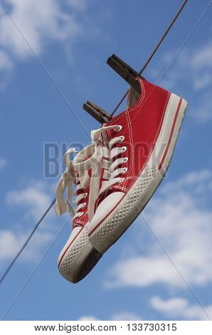 pair of red sneakers hanging on a clothesline on a blue sky background