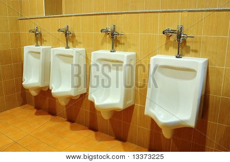 white urinals in the bathroom at office