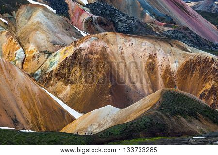 Hikers in colorful rhyolite mountains near Landmannalaugar Iceland