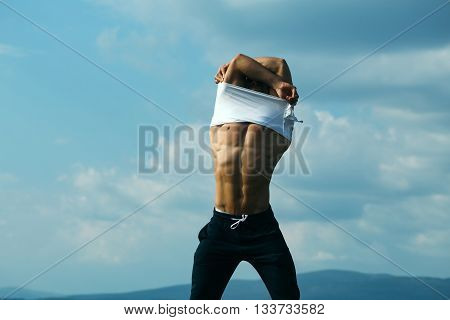 young macho man model athlete with muscular sexy body and wet bare chest outdoor on sky background undressing white shirt