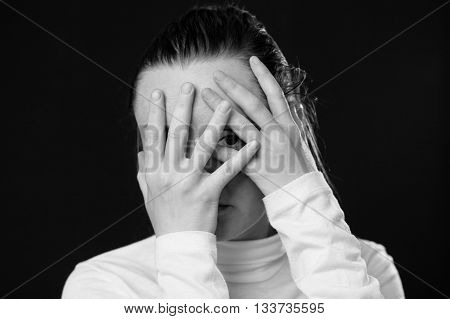 Close up portrait of a woman closing her face by the palms only one eye is looking to the camera dark background black and white