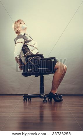 Afraid businesswoman bound by contract terms and conditions with mouth taped shut. Scared woman tied to chair become slave. Business and law concept. Instagram filtered.