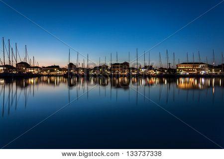A calm night in Lefkada, Greece. Yachts docked in the city marina.