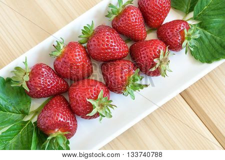 Strawberries with stems on a white platter
