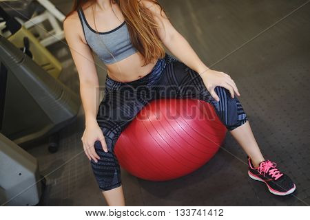 Attractive athlete young woman doing exercise at gym. Indoors.