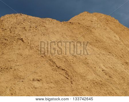 The proverbial dirt pile. This pile is more than fifty-feet height and  over 30 yards in length. The stormy sky ads contrasting background.