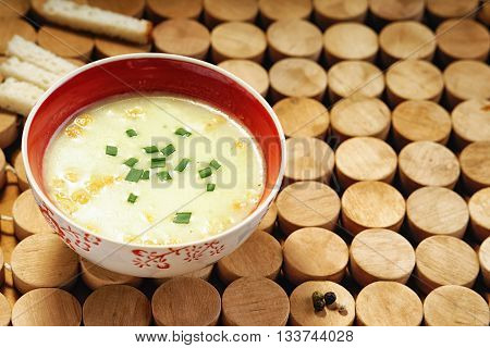Cream soup and bread croutons on a wooden circles textured tablecloth