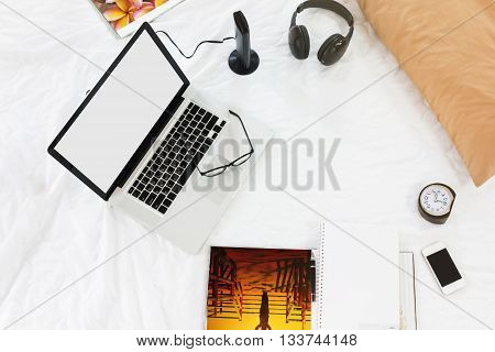 Blank screen laptop or notebook with all things around on bed in background work on bedmusic shopping online connected on bed miscellaneous on bed