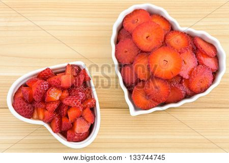 Sliced and diced strawberries in two white heart shaped bowls