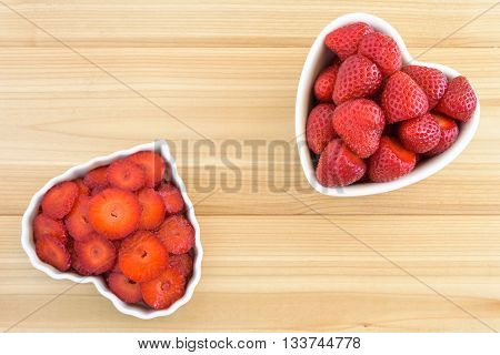 Whole and sliced strawberries in two white heart shaped bowls