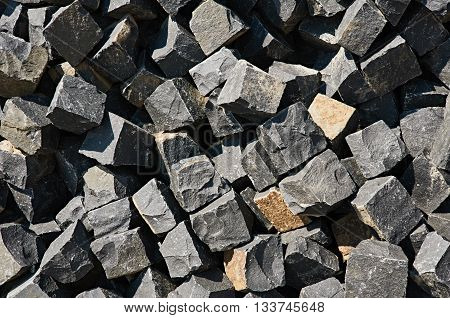 Pavement rocks, stones and cobblestone blocks are in lie in a heap