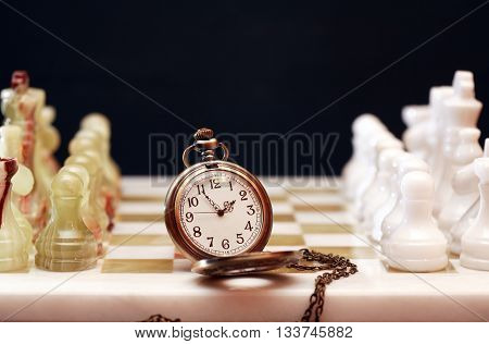Set of chess pieces made from Onyx near watch on board against dark background