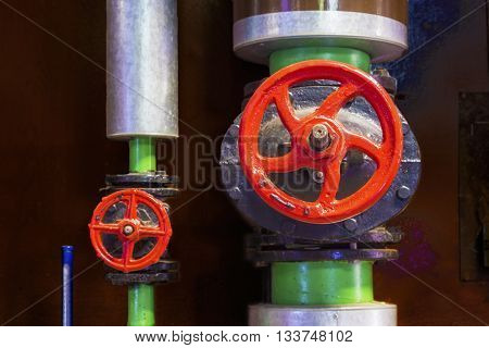 Close view of heating system's metal pipes with red cast-iron valves and blue mercury thermometer