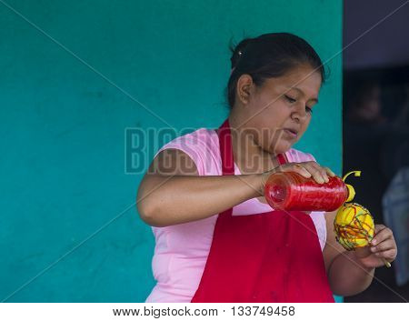 PANCHIMALCO EL SALVADOR - MAY 08 : A Salvadoran woman sells mango on a stick during the Flower & Palm Festival in Panchimalco El Salvador on May 08 2016