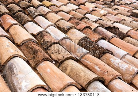 Old weathered and discolored clay roofing tiles detail with rows of overlapping semi circular curved tiles on a roof in a full frame view