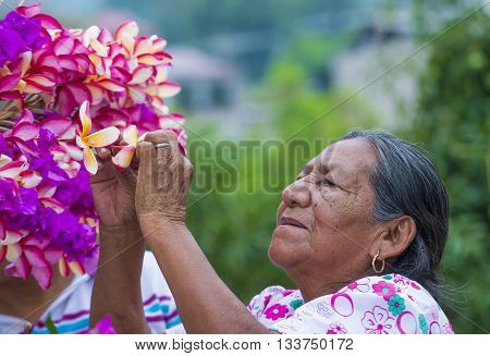 PANCHIMALCO EL SALVADOR - MAY 08 : A Salvadoran woman decorates palm fronds with flowers during the Flower & Palm Festival in Panchimalco El Salvador on May 08 2016