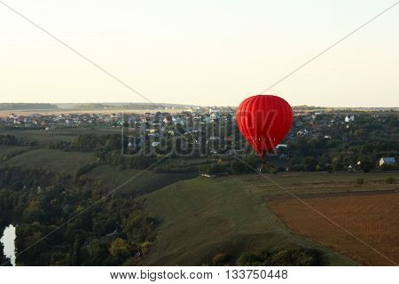 Hot air balloon (aerostat) over green fields and a city behind it