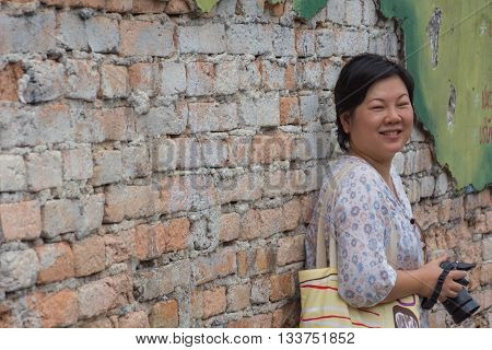 Asia woman plump body holding a DSLR camera standing against a vintage red brick wall when travel