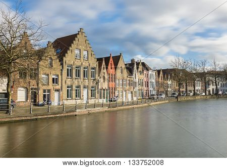 Bruges - circa February of 2016, Belgium: Old houses and their reflections in water on Langerei street in Bruges