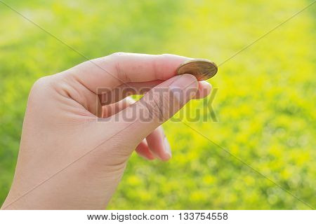A female (woman) hand hold a coin in green grass background. Save money saving money concept.