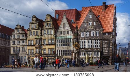 Bremen, Germany, 17th April 2016. Main market square with the famous statue 'Roland of Bremen' in the middle of it. People walking and standing in front of old historic buildings in the background.