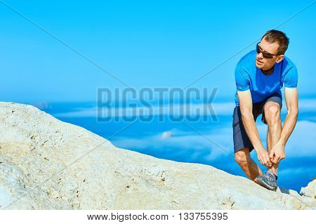 man runs on a rock against a blue sea. man leaned lace up sneakers