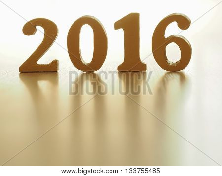 Text of gold 2016 make from wood. Golden year 2016. New year decoration closeup on 2016 text. Happy new year 2016. Gold 2016 on wood floor with copy space at the bottom for your text.
