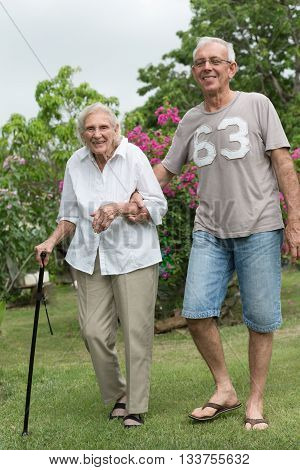 Man helping happy senior lady walking in garden