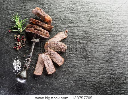 Steak Ribeye with spices on the graphite board.