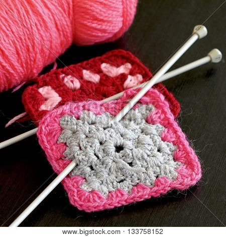 Hand knitted pink and grey square with needles.