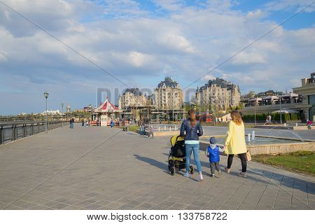 KAZAN, RUSSIA - APRIL 30, 2016: People walk on the embankment of the Kazanka river, spring day. Modern Kazan