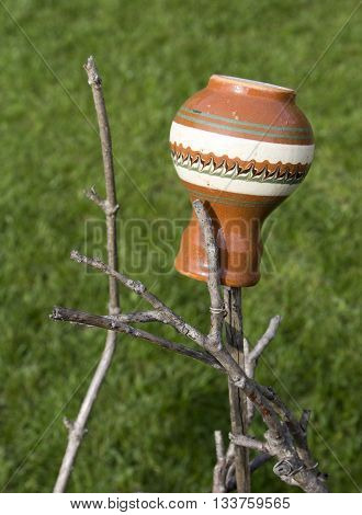Ceramic jug hung on a stick against grassy background
