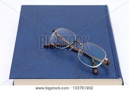 Glasses and book on the white wooden table