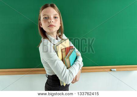 Haughty student hugging books. Photo of teen near blackboard education concept