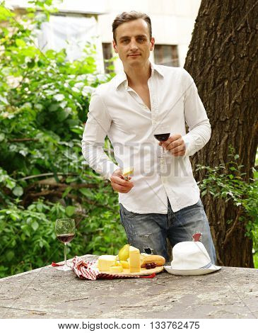 Young man tasting red wine with cheese board, outside in the garden