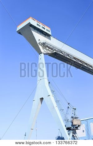 Wharf or shipyard of Hamburg Harbor, Germany. Harbor crane at a commercial dock.
