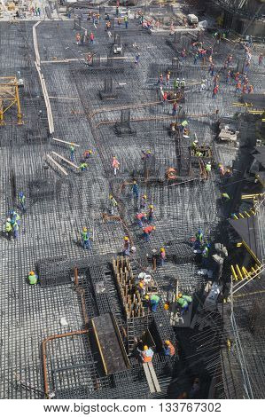 Dubai, United Arab Emirates - October 16, 2014: Workers preparing steel reinforcement for foundation of a new building.
