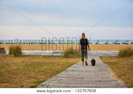 Woman And Dog Walking To The Beach