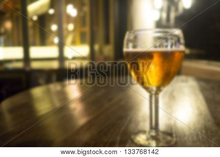 Blurred vintage glass of light beer on wood table in a pub restaurant