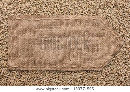 Pointer of burlap lying on a rye background with place for your text