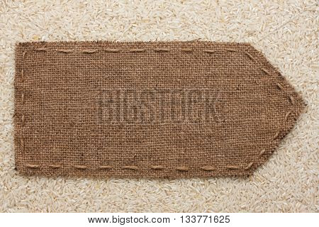 Pointer of burlap lying on a rice background with place for your text