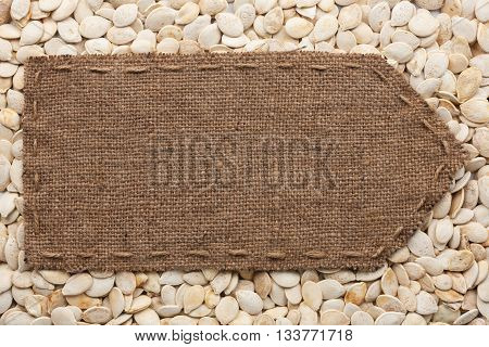 Pointer of burlap lying on a pumpkin seeds background with place for your text