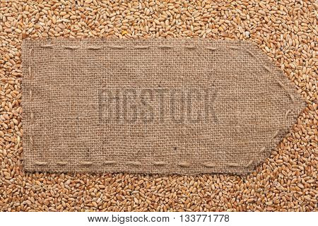 Pointer of burlap lying on a wheat background with place for your text