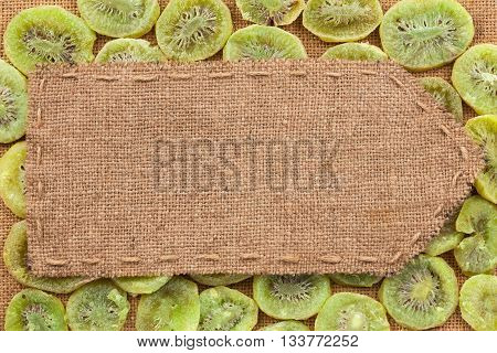 Pointer of burlap lying on a dry kiwis background with place for your text